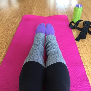 Legs from the knee down, in yoga pants, leg warmers, and purple socks on a pink yoga mat atop a hard wood floor