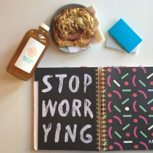 """Paper planner says """"Stop Worrying"""" with kombucha bottle and a breakfast sandwich"""