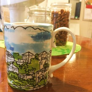 hand painted Anthropologie mug sits on a coffee table with water pitcher and nuts in a jar in the background